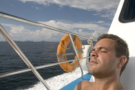 yachtsman: young man tanned at a cruise boat