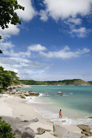 Girl on a clear water beach with rocks, Phuket Island, Thailand