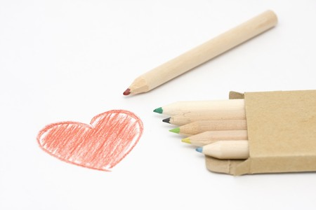 a red heart sketched and an assortment of coloured pencils with shadow on white background, ideal for valentine day Stock Photo