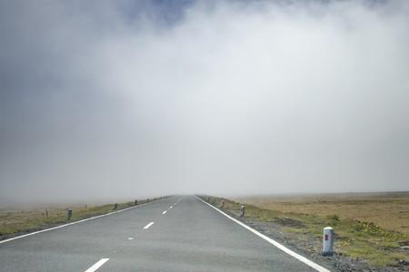 Road vanishing to the horizon under foggy scenery Stock Photo