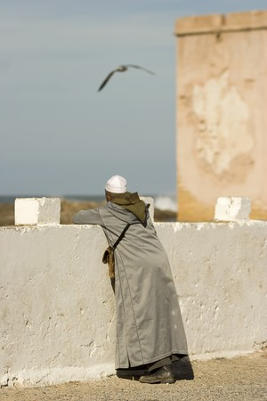 berber man standing on a beach and looks into the ocean, Morocco Stock Photo
