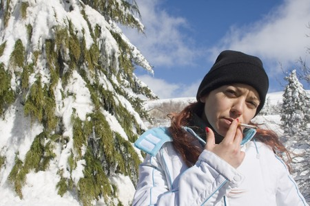 Young woman at a snow park smoking a cigarette Stock Photo
