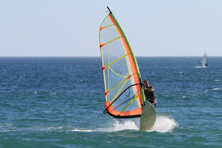 summer sports: windsurfer with bright colored sail on Algarve blue water, south of Portugal Stock Photo