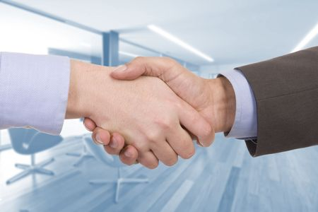Handshake of two successful businesspeople (with office on background) Stock Photo