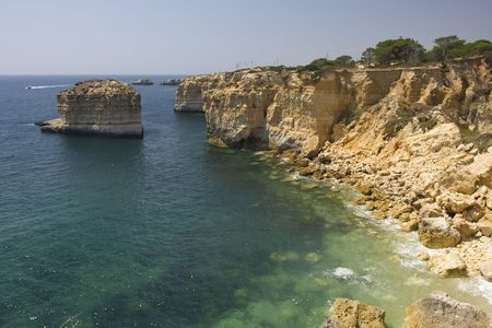 Beautiful view of an idyllic wild beach in summertime - sand and sea at Algarve, Portugal coast.