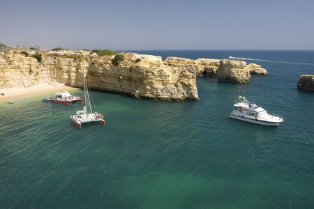 Beautiful view of an idyllic wild beach in summertime with boats - sand and sea at Algarve, Portugal coast.