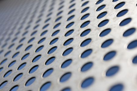 Bright brushed and drilled a hole metal texture over a blue background (selective focus, photographed with shallow DOF) Stock Photo - 6796381