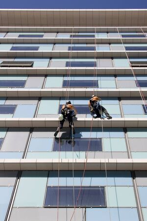 Workers washing the windows facade of a modern office building (cleaning glass service) Stock Photo