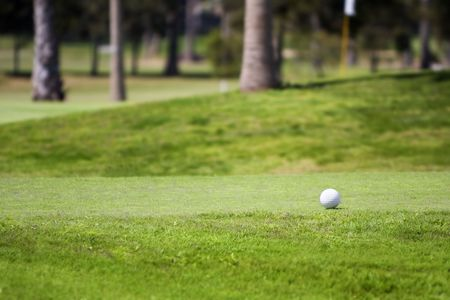 Golf ball on tee in a beautiful green grass golf course,photographed with shallow DOF (Lifestyle concept)