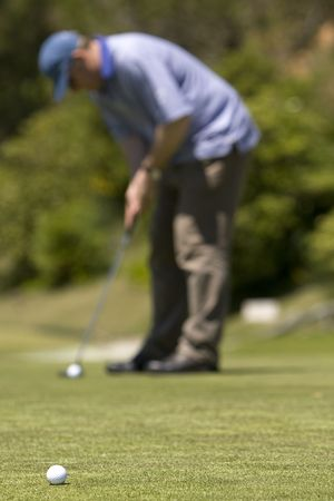 Man playing golf on a fresh green golf course, drive and ball