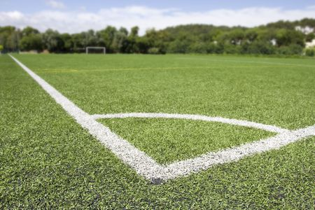 pitch: Green grass and corner lines of an outdoor football field (artificial covering)