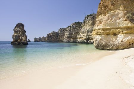 Beautiful view of an idyllic wild beach in summertime - sand and sea at Algarve, Portugal coast. Stock Photo
