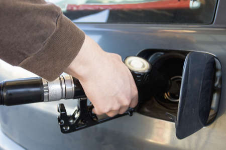 refueling: close-up of a mens hand refueling a car at a gas station (Fuel Pump)