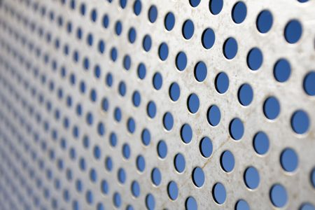 Bright brushed and drilled a hole metal texture over a blue background (selective focus, photographed with shallow DOF) Stock Photo - 6801398