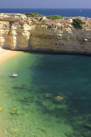 Beautiful view of an idyllic wild beach in summertime with boat- sand and sea at Algarve, Portugal coast.