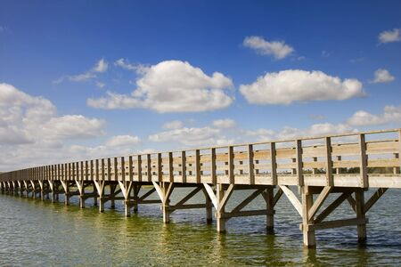Wooden bridge and rails. A pathway leading to the wild beach