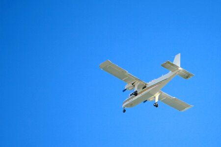 A light aircraft (small airplane) taking off into a clear blue sky.