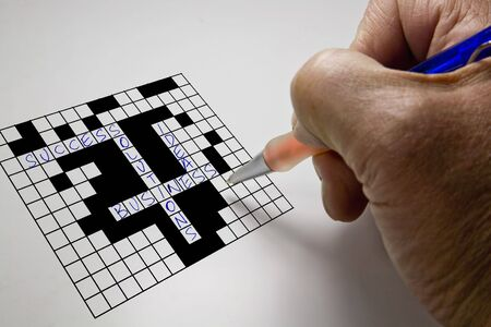 Crossword puzzle for the business man with pen in hand photo