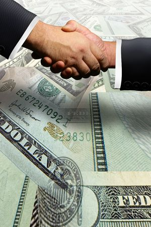 Two business men shaking hands over a money transaction