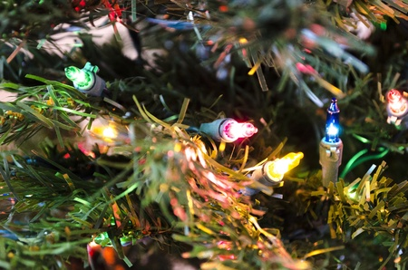 close up of multi colored miniature christmas lights on an artificial tree stock photo