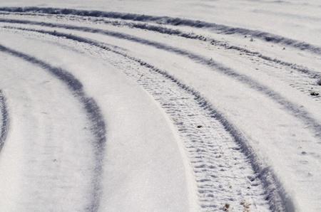 Bandensporen in de sneeuw op een landelijke weg Curves naar links