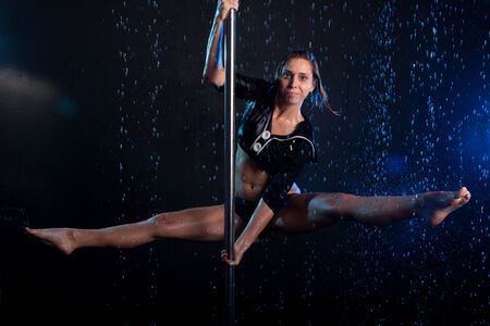 Young Young sexy woman pole dancer. Water studio photo sexy woman pole dancer. Water studio photo