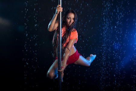 Young sexy woman pole dancer. Water studio photo