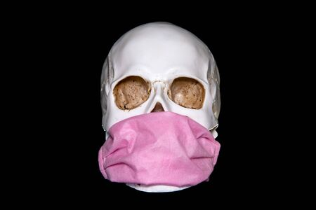 A human skull In Medical Mask on a dark background. Concept Of Deadly Coronavirus Epidemic. covid-19.