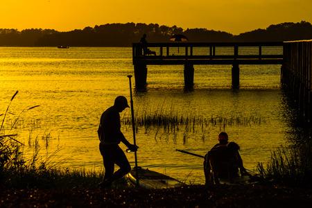 Kayakers at sunset near fishing pier on Hilton Head Island SC Stock Photo