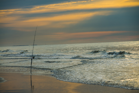 Surf fishing rod in the water at sunrise on Hilton Head Island SC.