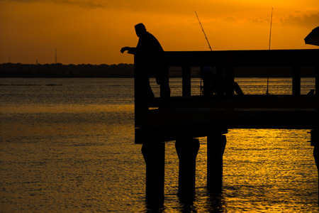 Silhouette of fisherman on pier,Intercoastel Waterway. Stock Photo