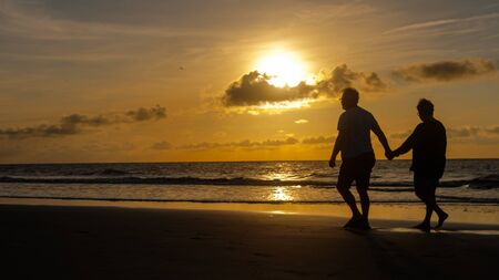 Couple holding hands walking on beach at sunrise on Jekyl Island GA.