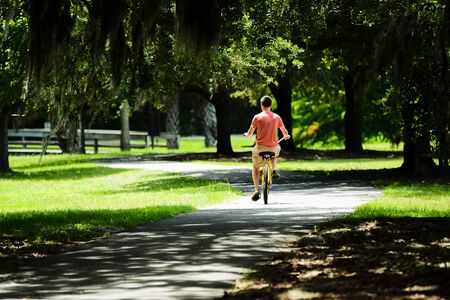 Picture from behind of your male riding a bike on a paved path through the trees and moss of SC. Stock Photo
