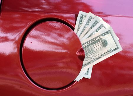 Twenty dollar bills sticking out of gas tank  signifying high cost of energy photo