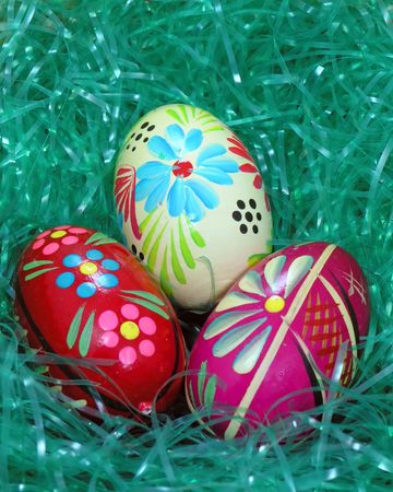 Three hand painted wooden Easter eggs over grass photo
