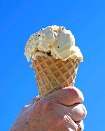 青い空を背景にアイス クリーム コーンを持っている手