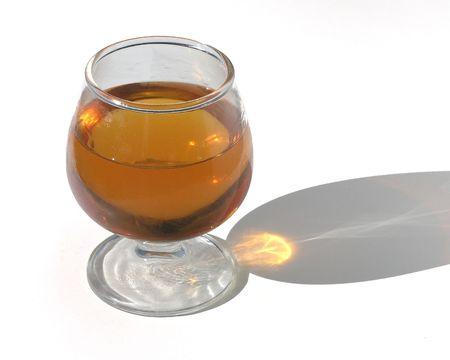 sun lit: Sun lit brandy glass and shadow over white