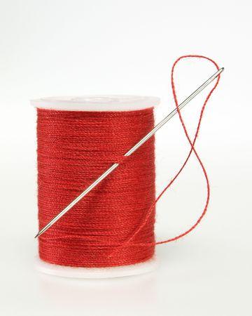 ホワイト上のスレッドの針と糸の赤いスプール 写真素材