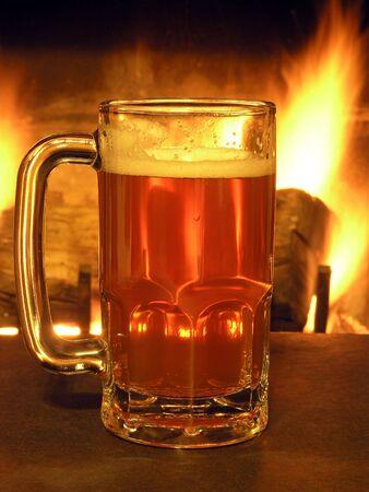 非常に熱い丸太の暖炉照らされて戻ってビールのジョッキ