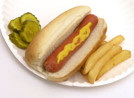 Hot dog with mustard, fries and pickles on a paper plate