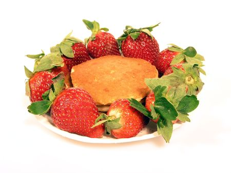 luscious: Luscious red strawberries surrounding golden brown pancakes isolated over white