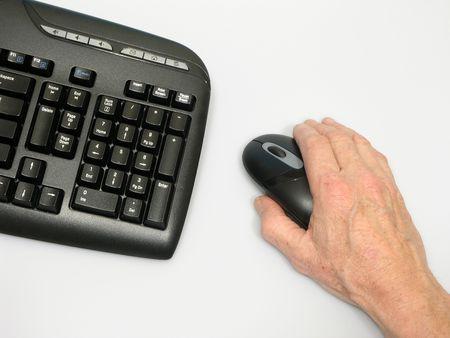 ワイヤレス キーボードの側に沿ってコードレス マウスを握る手します。