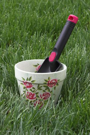 Hand shovel planting tool in flower pot with green grass background