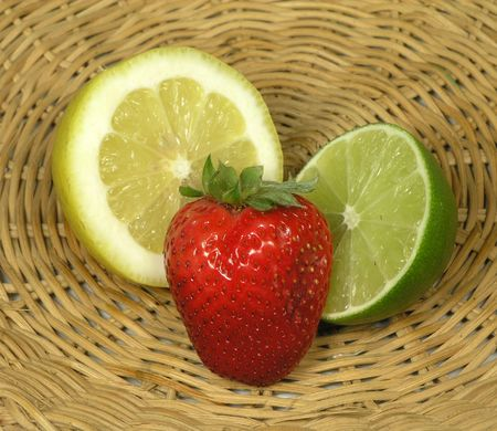 scurvy: Cut lemon lime and whole strawberry on a straw platter Stock Photo
