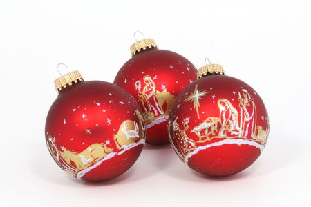 three red ornaments depicting nativity scene over white stock photo