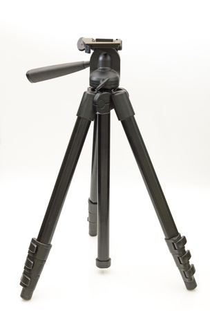 Black carbon fiber camera tripod over white