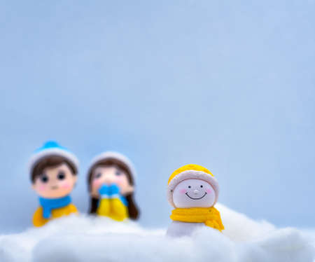 Tourism and travel concept: Miniature little snowman in winter snow with couple in the background Foto de archivo