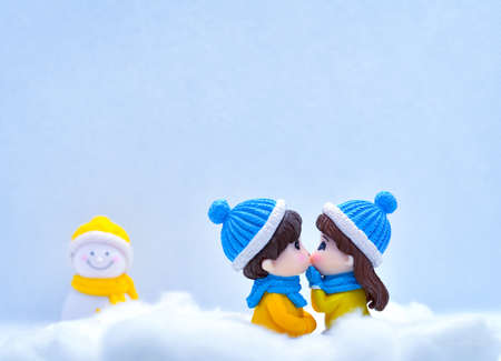 Tourism and travel concept: Miniature people kissing each other in winter snow with little snowman in the background