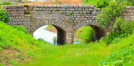 Old stone single arch bridge, Latvia. Famous ancient stone arch single track road bridge in the forest. View of small river and trees reflection in the water.