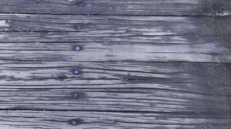 A background of weathered planks.  Deep grained wood pattern.  Primarily black in color, row of nail heads vertically. Stock Photo
